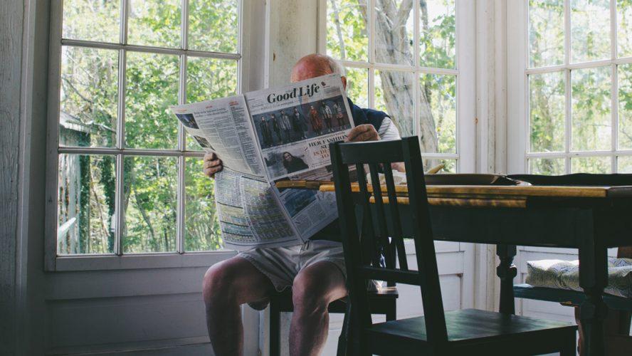 Äldre man läser tidningen.