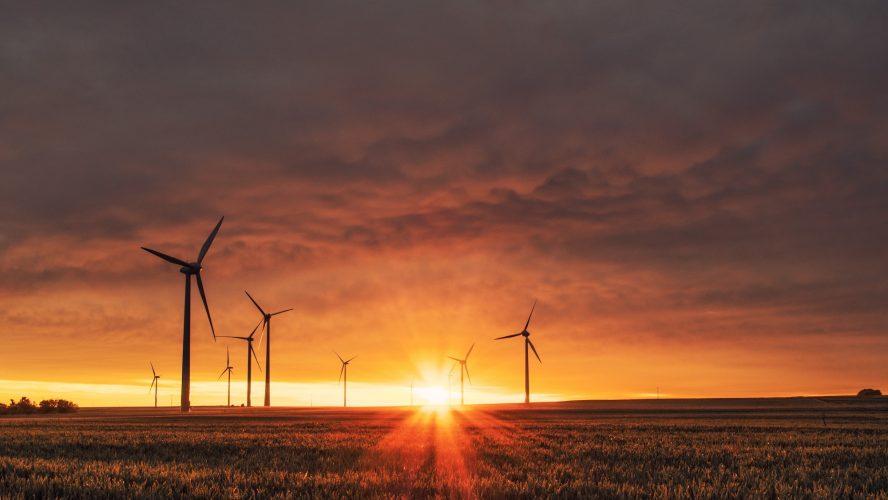 Vindkraftverk i röd solnedgång för att relatera till grön innovation