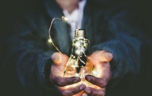 Händer som håller i en glödlampa med lunchslinga