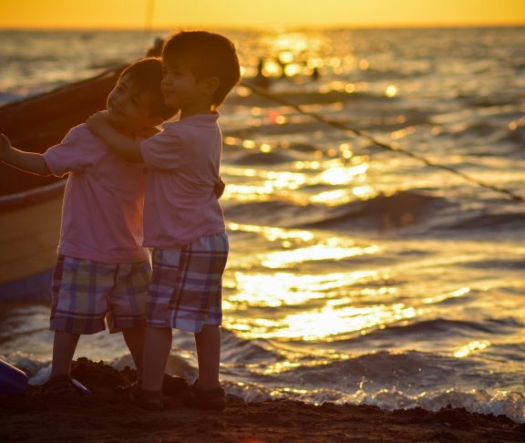 Två pojkar som leker i solnedgången