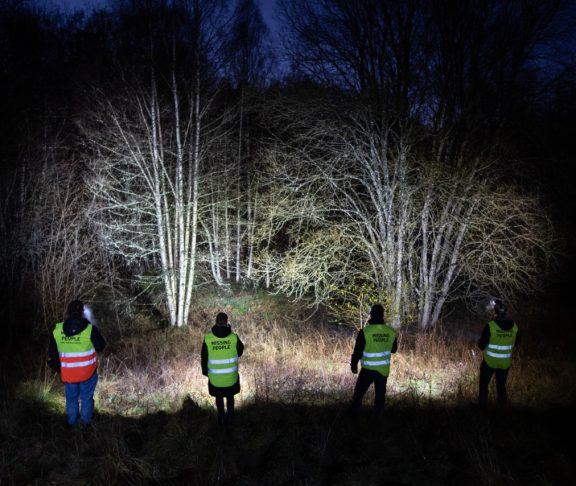 Missing People volontärer som lyser med ficklampor i mörkret
