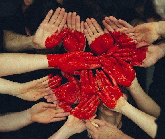 Flera händer tillsammans med röd färg som bildar ett hjärta för ideellt engagemang