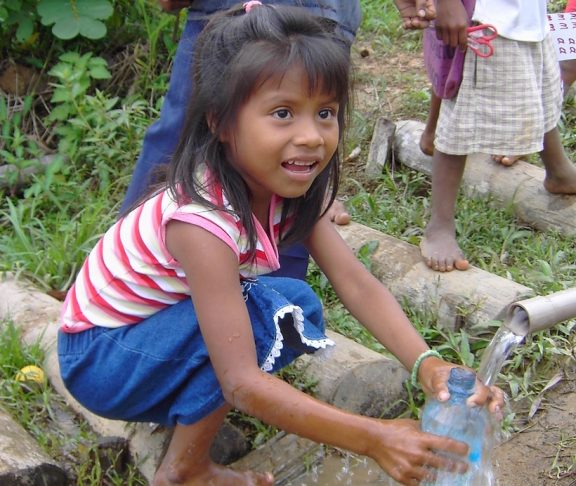 Flicka som sitter på huk och får rent vatten ur ett rör