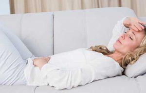 kvinna som ligger i soffan och tar sig för magen