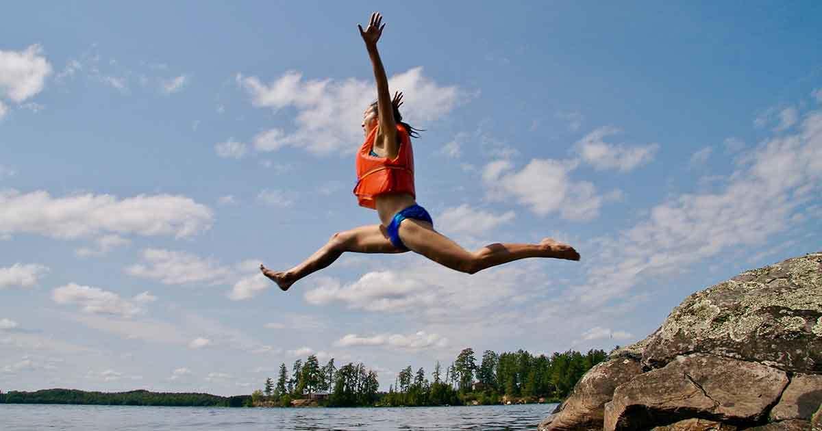 Kvinna som hoppar med flytväst