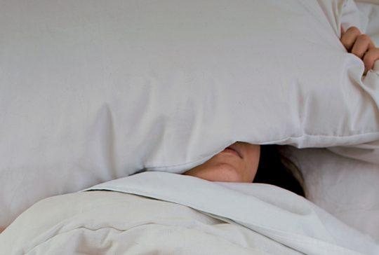 Kvinna som sover med kudden över huvudet.