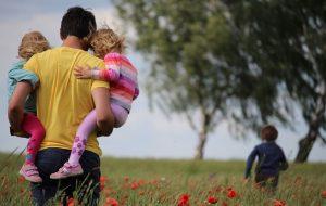 En pappa på en äng som bär sina barn.
