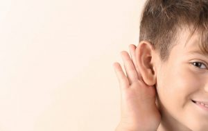 Cute,Little,Boy,With,Hearing,Problem,On,Light,Background,,Closeup.
