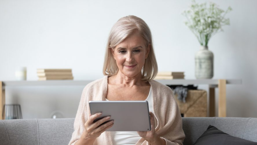 Portrait of pleasant middle aged woman sitting on cozy sofa, using tablet computer at home. Happy female retiree web surfing information, shopping in popular online store, reading electronic book.