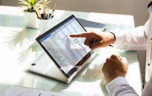 Businessman's hand analyzing gantt chart on laptop over reflective desk