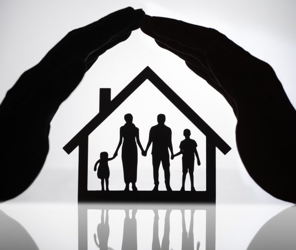 Silhouette Of A Person's Hand Protecting House With Family Figures