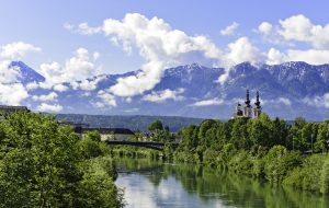 The Alps in Villach - mountain range in the clouds with a small chapel on the bank of the river