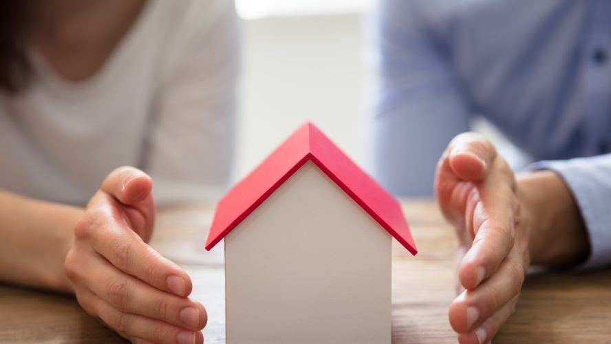 Couple's Hand ProtectingHouse Model Over Wooden Desk