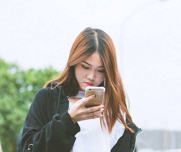 Kinesisk kvinde kigger på sin smartphone