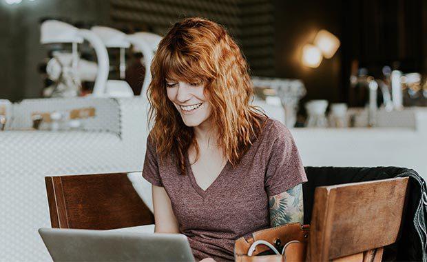 Kvinna med laptop på cafe
