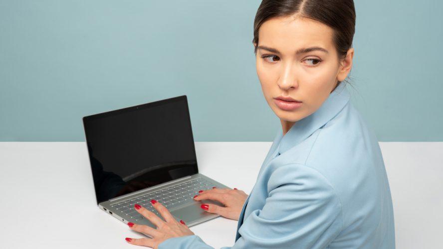 Kvinna vid dator som kollar över axeln.