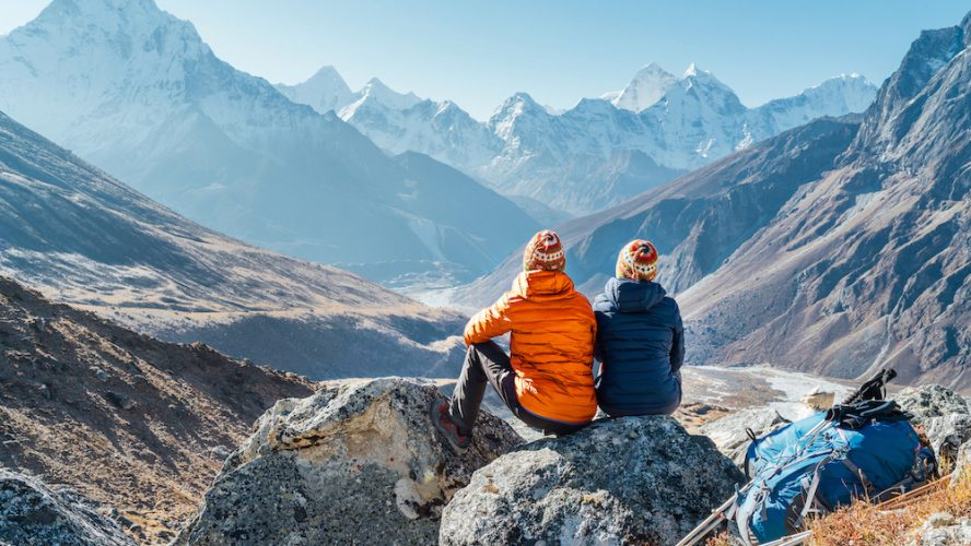 Couple resting on the Everest Base Camp trekking route near Dughla 4620m. Backpackers left Backpacks and trekking poles and enjoying valley view with Ama Dablam 6812m peak and Tobuche 6495m