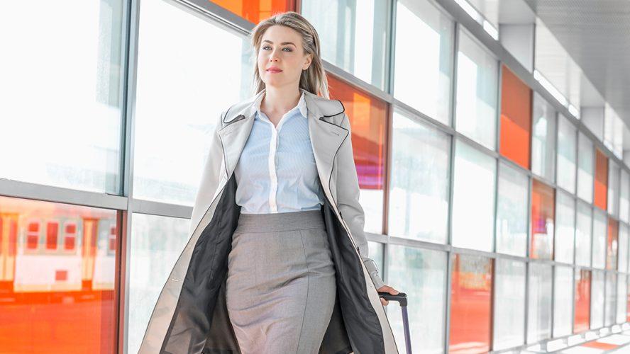 kobieta idąca holem na lotnisku z bagażem w dłoni