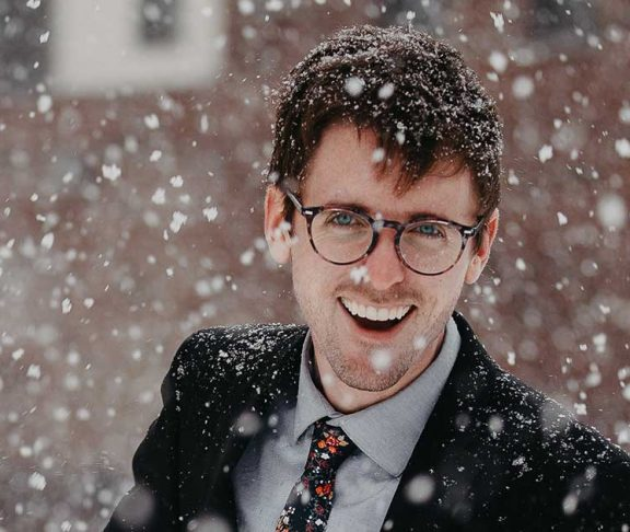 Glad mand ude i snevejr. Klar til at hoppe i bilen