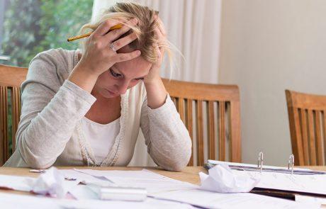 Frustreret kvinde med et hav a regninger foran sig