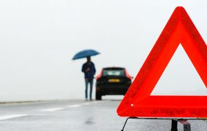 Mand med paraply og nedbrudt bil i regnvejr
