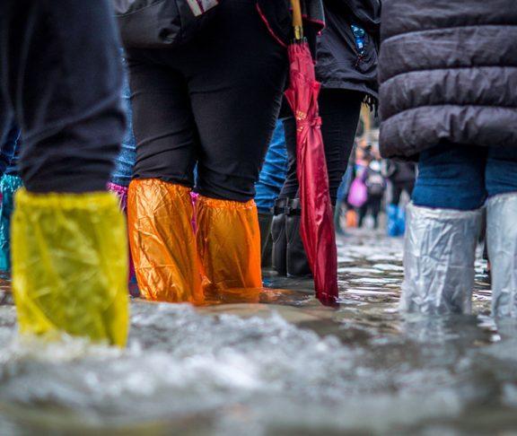 Mennesker står i vand til knæene