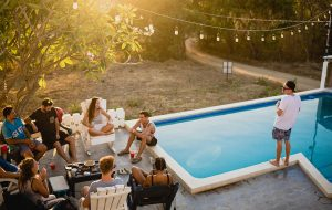 Selskab hygger i sommerhus med pool