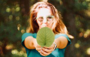 Kvinde holder grønt blad frem mod kameraet