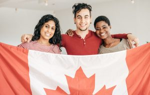 Three new Canadians holding a flag
