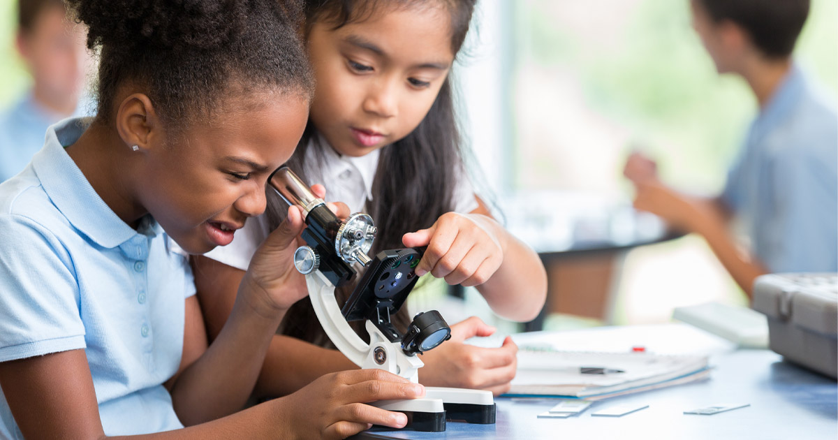 Two younng girls using a microscope