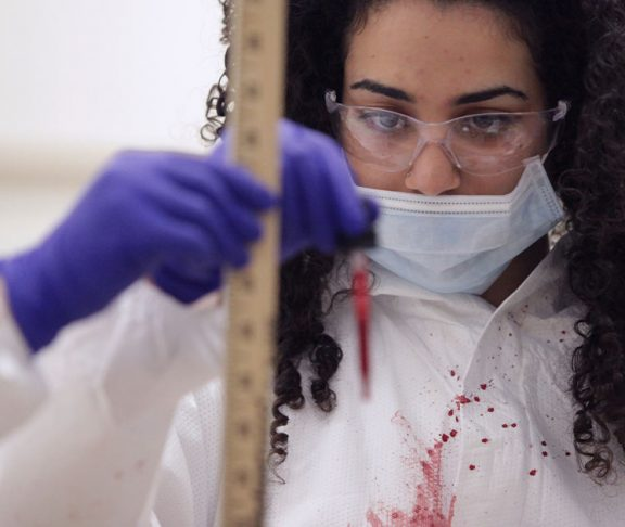Female student learning about blood spatter patterns