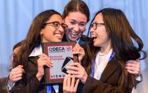 Three girls clutching the DECA Provincial Champion award