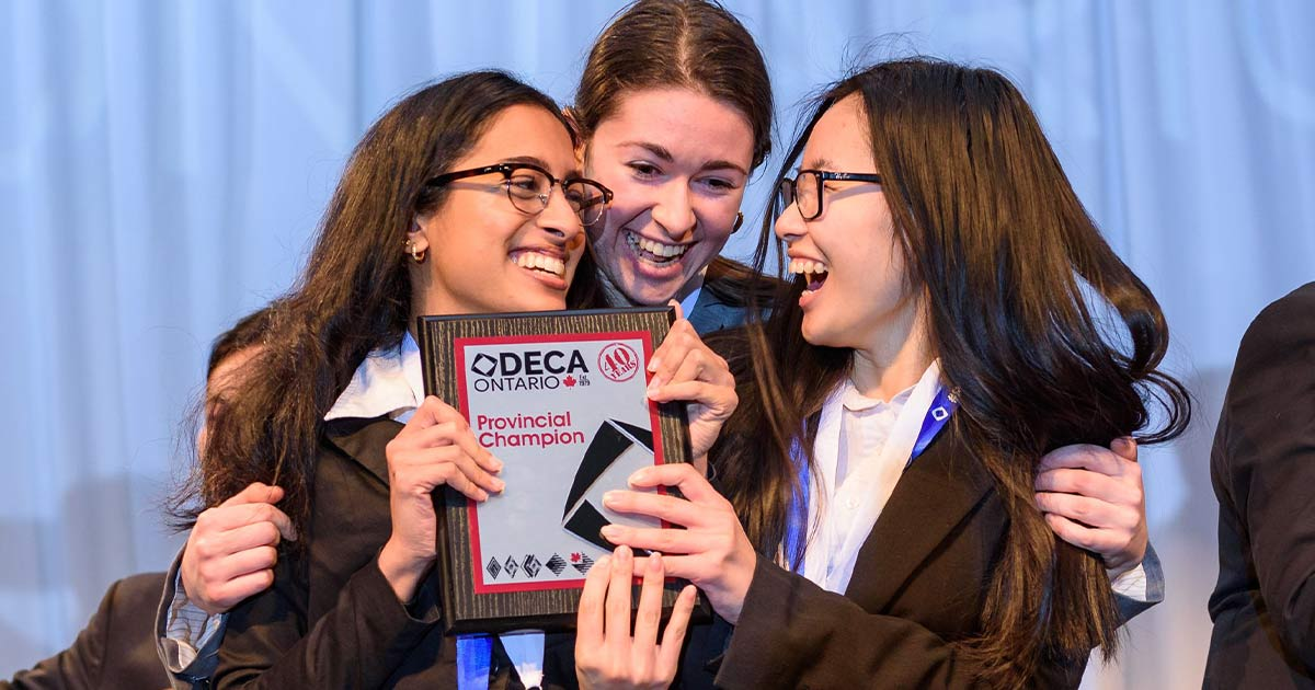 Three girls clutching the DECA Provincial Champion award