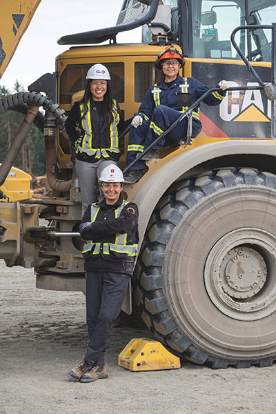 Three smiling construction workers on a CAT