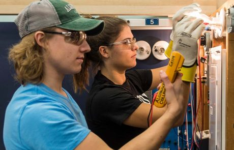 Two students learning hands-on electrical work