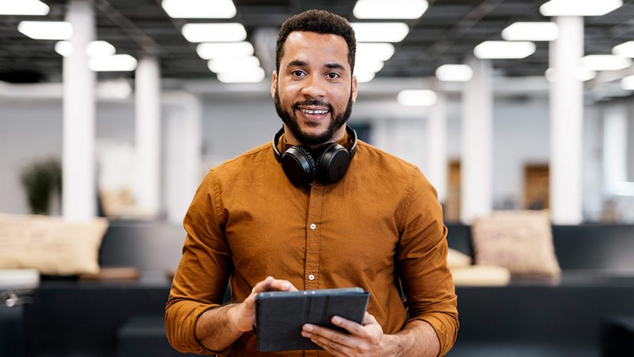 Man in an office smiling and holding a digital tablet