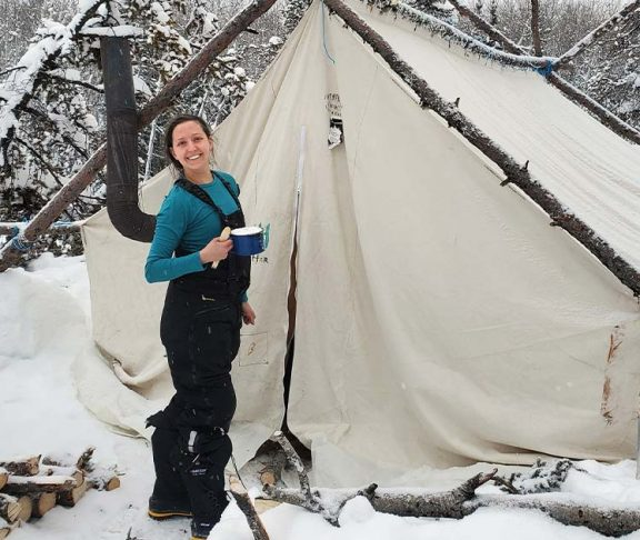 Aurora College student standing outside a tent in a snow and grinning