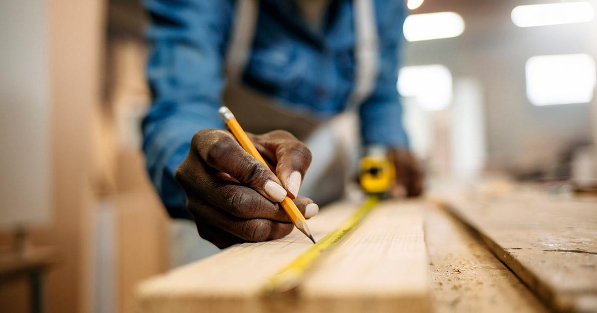 Carpenter marking measurements on wood