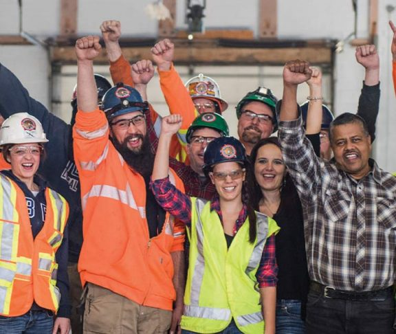 IBEW Local 353 members pumping their fists in the air