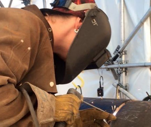 Jill Timushka welds the open root on a pipe in the 5g position