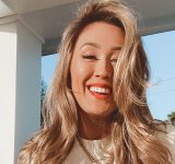 Lauren Riihimaki smiling on a porch