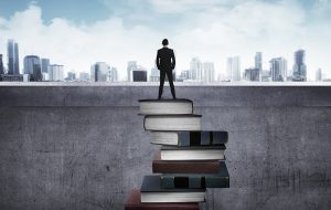 A man standing on a foundation of books while facing the world