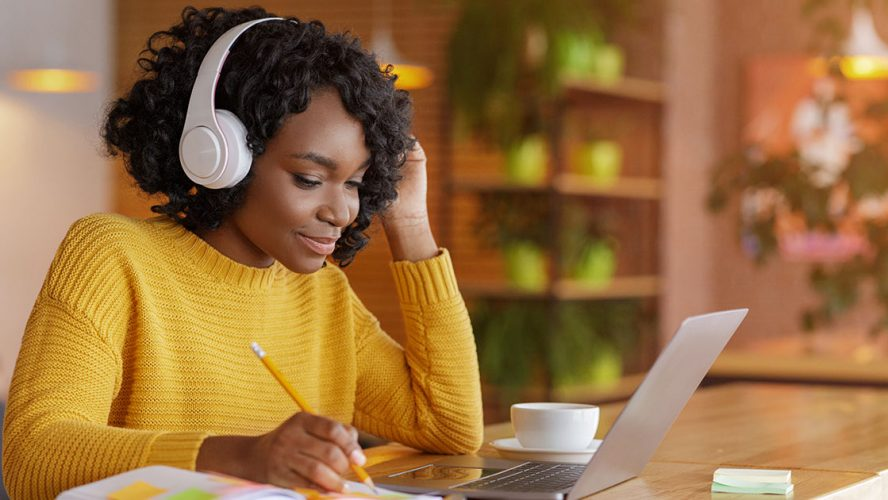 Woman wearing headphones and working on laptop