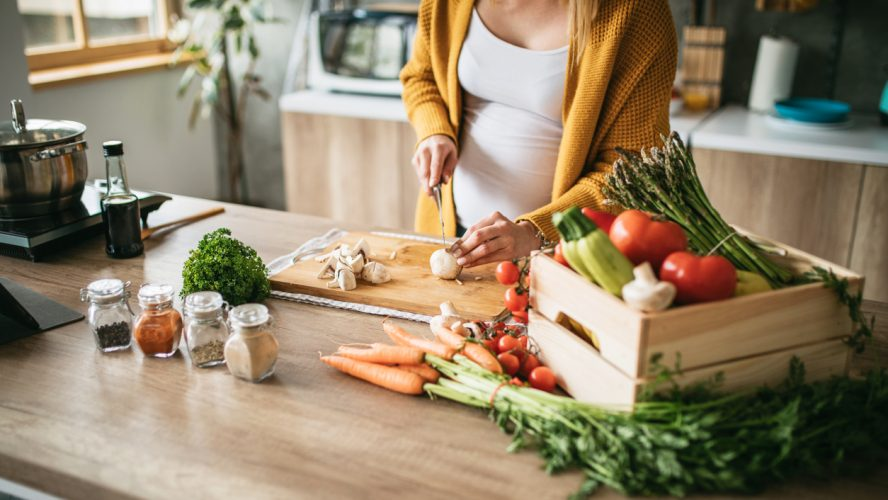 Beautiful pregnant woman following the recipe while cutting mushrooms in the kitchen