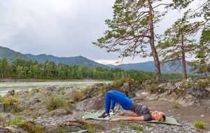 Blond beautiful girl is making a warm-up lying on the stone ground in the pose of the bridge, resting his palms and shoulder blades outdoors in the mountains near the river. Workout in nature.