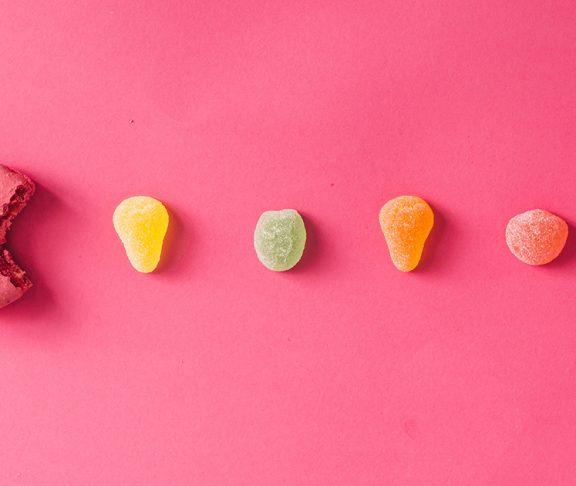 draże i cukierki na różowym tle