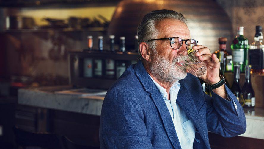 Eldre mann i bar drikker alkohol