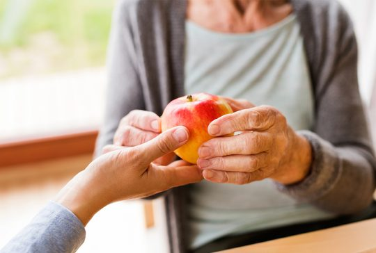 Gammel dame tar i mot eple
