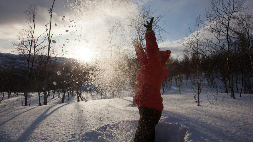 Barn kaster snø opp i luften