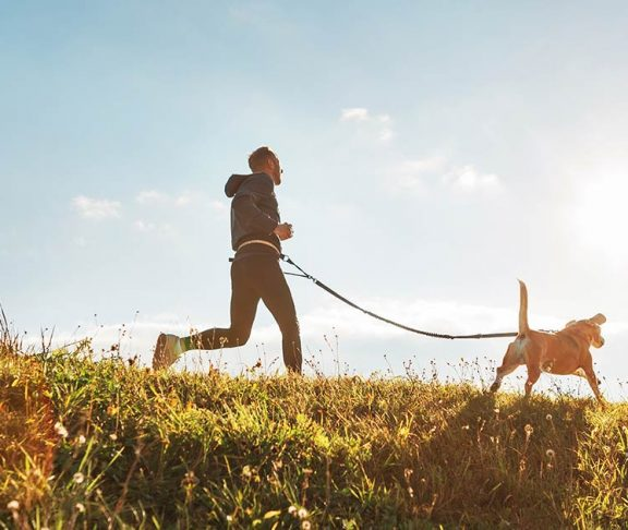Man and his dog running through a field